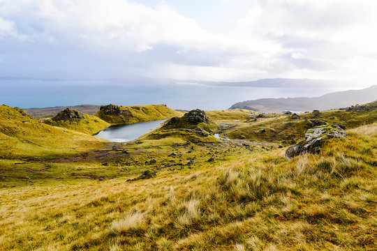 Landscape view with grass tussocks, rocks and sea of Isle of Skye, Scotland