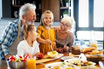 Happy grandparents with grandchildren making breakfast in kitchen