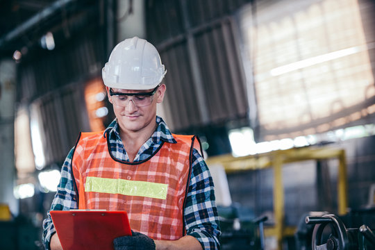 Engineering or technician man worker in hard hat and protective uniform working with document in manufacturing industrial factory. smart manager or leader checking on construction repair checklist