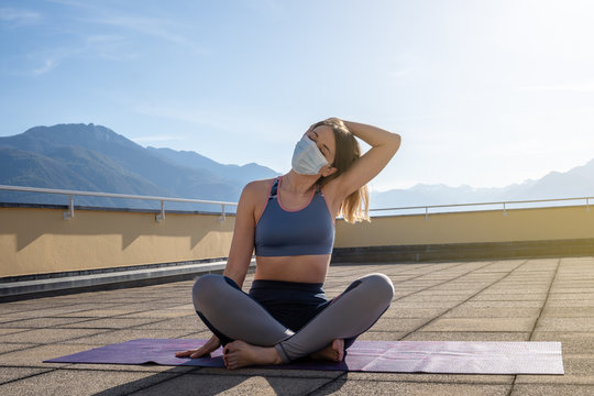 young woman exercising on terrace with face mask