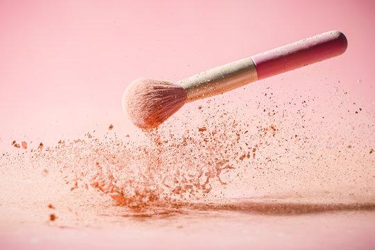 Make up brushes with powder splashes isolated on pink background