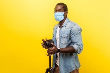 Portrait of excited motivated photographer or video blogger with surgical medical mask smiling and at camera with professional digital dslr camera on tripod. studio shot isolated on yellow background