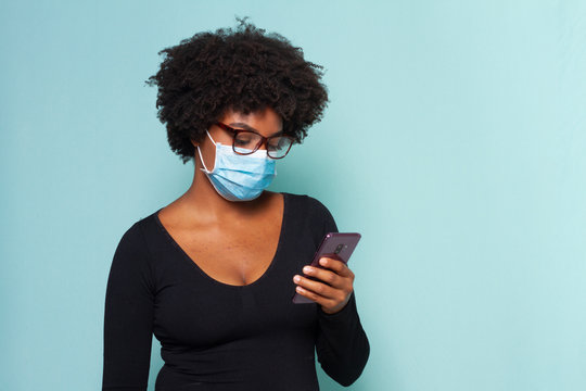 black woman with black power hair wearing protective mask with smartphone in hands and wearing reading glasses