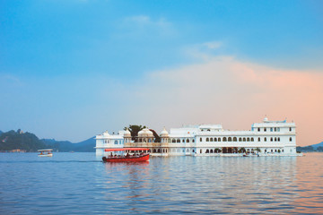 Wall Mural - Romantic luxury India travel tourism - tourist boat in front of Lake Palace (Jag Niwas) complex on Lake Pichola on sunset with dramatic sky, Udaipur, Rajasthan, India