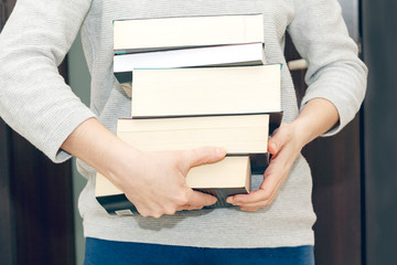Woman carrying a pile of thick books for reading