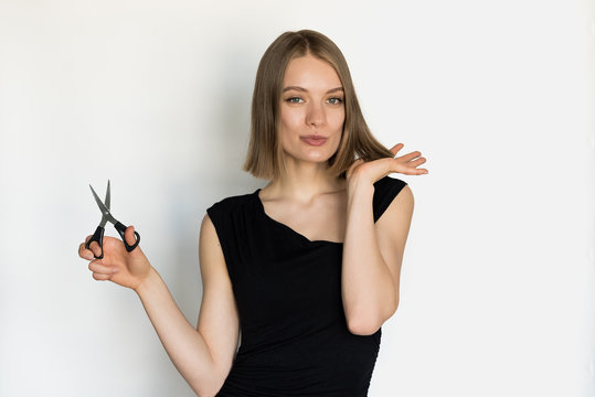 Young woman cuting her own hair on short and being suprised