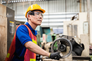Portrait of smart asian industrial worker wearing uniform and yellow safety helmet with looking to camera and smile. Industry, Engineer, construction concept.