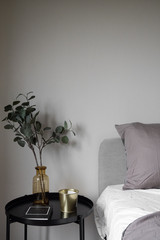 Bedroom corner grey velvet bed with soft pillows setting decorated with circular metal night table and beige painted wall in the background / cozy interior design
