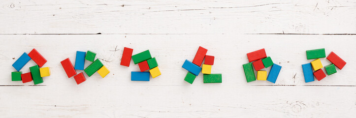 Top view on wooden colorful bricks on a white wooden background. Different-colored wooden blocks are scattered on the table. School, education and learning concept.
