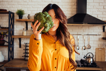 A portrait of nutritionist with a broccoli in the hand. Beautiful women in a yellow dress.