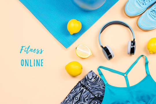Fitness equipment and workout accessories with clothes flat lay. Online workouts at home during quarantine concept. Top view, staying healthy, practicing sport background with fitness online text