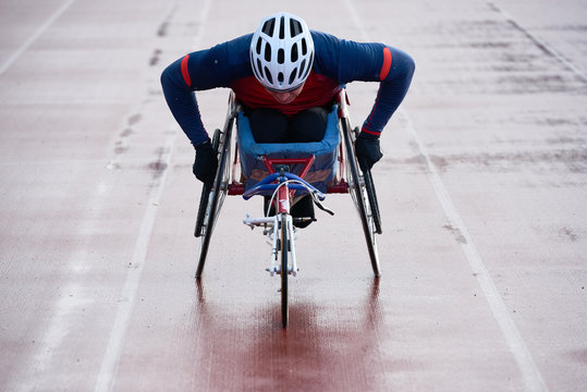 Paraplegic male athlete training speed while racing in sport wheelchair