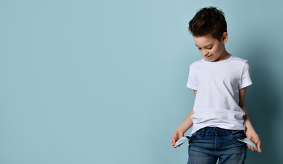 Small cute boy with modern hairstyle in white t-shirt standing and showing empty pockets with no money concept