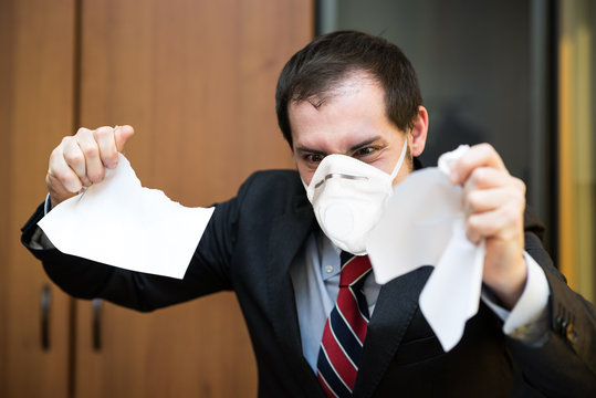 Angry masked business man destroying a document