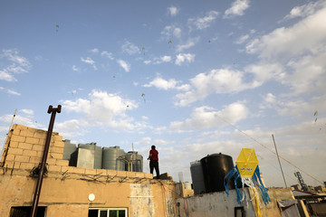 """People fly kites with """"Stay at home"""" phrases in Amman"""