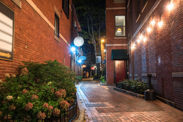 Narrow alley between old brick buildings with shops and restaurants on the ground level at night