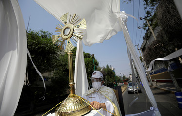 Angel Lauro Sanchez, parish priest of Catholic Church of Lady of the Rosary, performs procession in the streets with image of Sacrament Jesus to pray for soon dissipate the current situation of coronavirus pandemic (COVID 19), in Mexico City