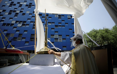 Angel Lauro Sanchez, parish priest of Catholic Church of Lady of Rosary, performs procession in streets with image of Sacrament Jesus to pray for soon dissipate current situation of coronavirus pandemic (COVID 19), in Mexico City