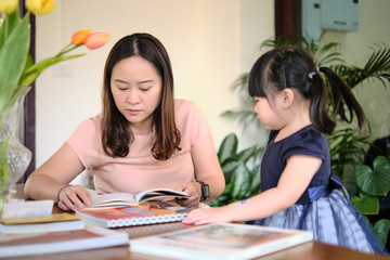Cute asian girl with mother learning by reading and studying books and playing at home in the living room, home schooling education for children, feeling happy cheerful, and enjoying staying at home
