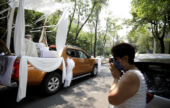 A woman prays as Angel Lauro Sanchez, parish priest of Catholic Church of Lady of Rosary, performs procession in streets with image of Sacrament Jesus to pray for dissipation of current coronavirus pandemic in Mexico City