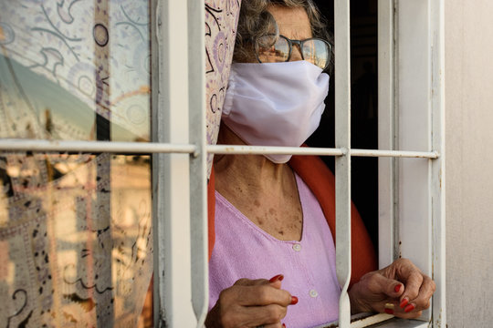 Grandmother with protective mask looking out the window. old woman looking outside isolated. Elderly woman