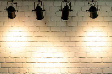 Hanging spotlight illuminate at brick wall background with copy space