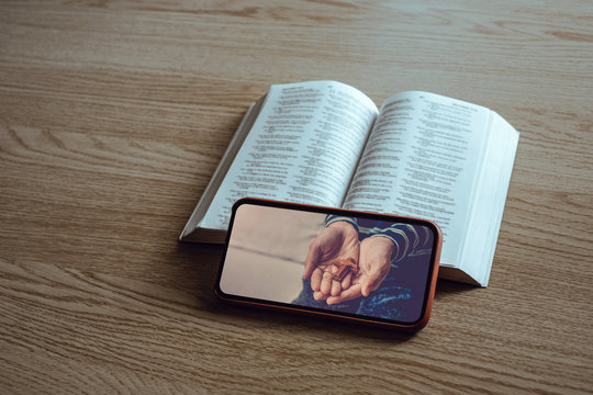 Worship from home, Online live church for sunday service, Top view of mobile screen with close up prayer hands and bible with wooden cross, quarantine for Covid 19 situation