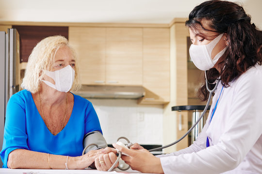Young doctor in medical mask checking blood pressure of senior patient during pandemic period