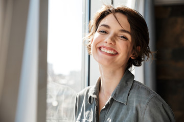 Image of beautiful young joyful woman smiling and looking at camera