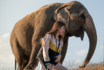 Young woman with elephant in Thailand.