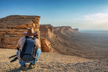 An adventure photographer in Edge of the World, a natural landmark and popular tourist destination near Riyadh -Saudi Arabia. Fototapete
