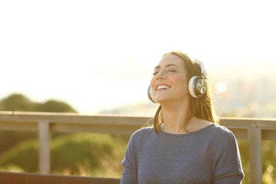 Happy girl listening music on headphones at sunset