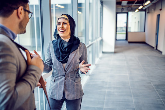 Attractive smiling arab woman talking with real estate agent about building she visiting. Hall of building in construction process interior.