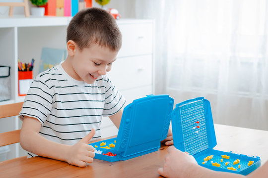 Boy child with dad playing warships and submarines are placed on the playing field in the game battleship. entertainment