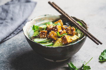 Vegan tofu poke bowl with rice, cucumber, avocado and nori, gray background.