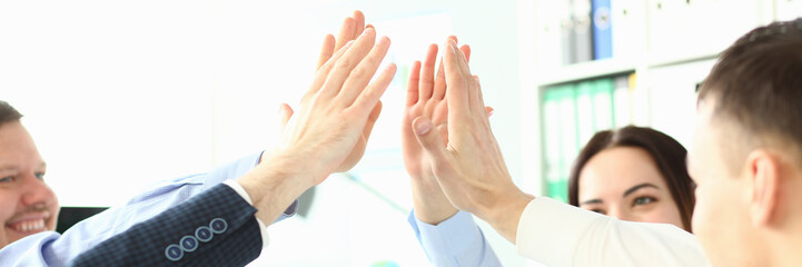 Focus on smart colleagues doing high five gesture in order to cheer collective up. Witty men and women celebrating finish of profitable project. Company meeting concept Fotobehang