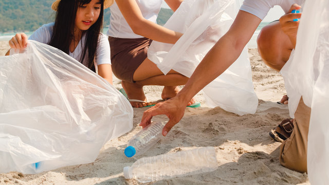Asian young happy family activists collecting plastic waste on beach. Asia volunteers help to keep nature clean up and pick up garbage. Concept about environmental conservation pollution problems.