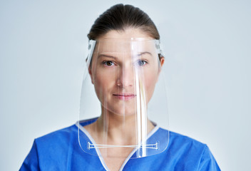 Close up portrait of female medical doctor or nurse wearing face shield