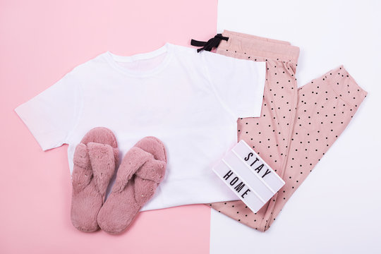 A t-shirt and sweat pants on pink and white background.  Flat lay, top view.