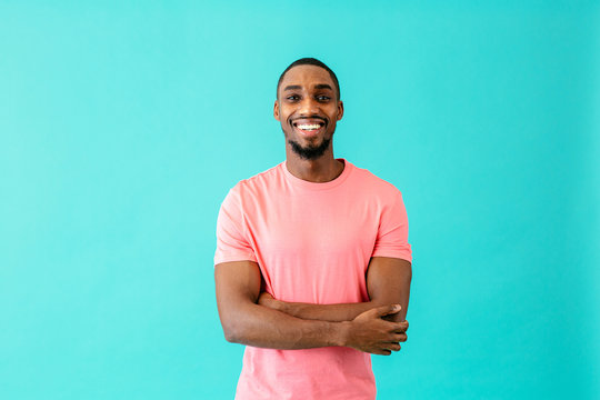 Portrait of a happy young man smiling with arms crossed, against blue studio background