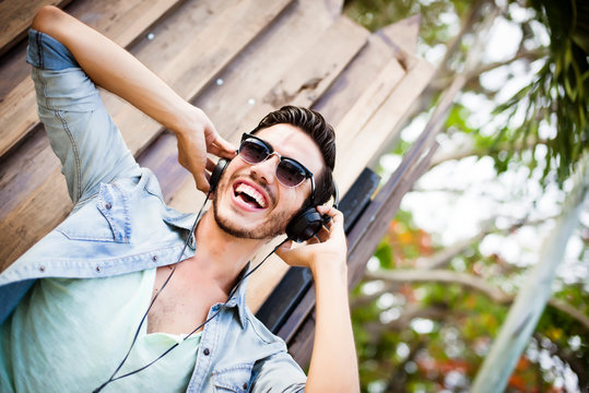 Young man listening music on the street - hipster style