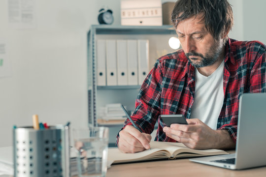 Freelancer writing notes and using smartphone in home office