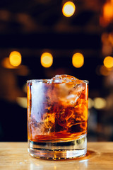 glass with whiskey and ice cubes on the bar with bokeh on background