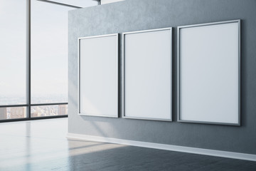 Minimalistic exhibition interior with city view and three empty banners.