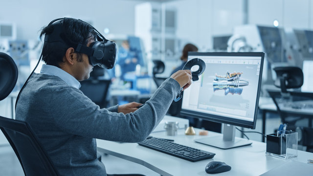 Modern Industrial Factory: Mechanical Engineer Wearing Virtual Reality Headset, Holding Controllers, Uses VR technology for Industrial Design, Development and Prototyping in CAD Software on Computer.