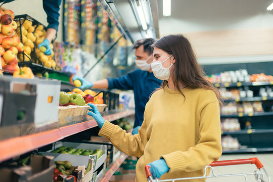 young woman in a protective mask buys apples