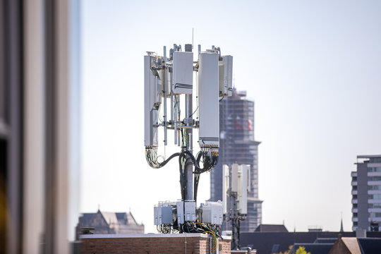 5g mobile tower installation with a clear sky in the background and the Dom tower of Utrecht