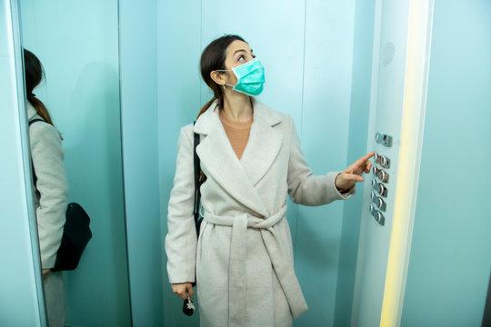 Donna vestita con un cappotto e mascherina prende l'ascensore