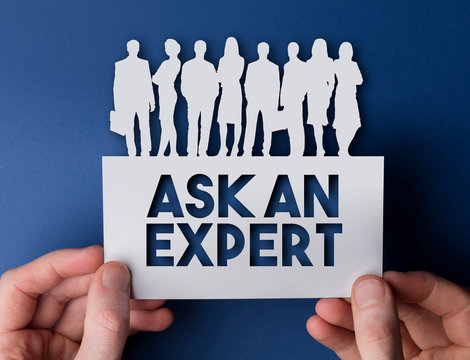 Hands holding an ask an expert white card business team people sign