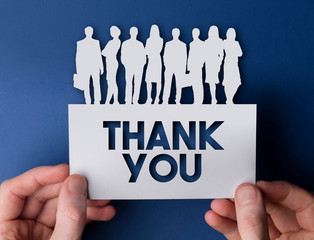 Hands holding a thank you white card business team people sign